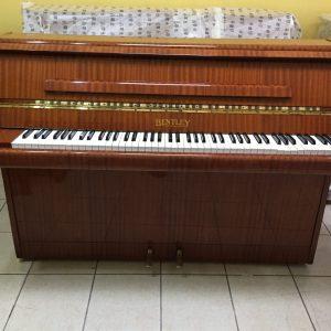 """El estilo """"The Concord"""" de este piano Bentley de 1978 es uno de los más elegantes pianos verticales diseñados por la compañía Bentley. Sus medidas son Alto: 110 cm (3'.7""""); Ancho: 143 cm (4' 8"""") y Profundidad: 53 cm (1' 9""""). El color es precioso! Un nogal vetado con un acabado vidrioso y pulido que lo hace ver muy elegante. Las teclas son de plástico y están intactas. La maquinaria está como nueva ya que no fue muy usado. Las cuerdas están como nuevas y los pines sin ninguna señal de óxido. En general el piano esta en excelentes condiciones."""