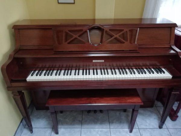 Este piano Fletcher & Sons de 39′ de algo es estilo consola. Tiene un riel principal de acción completo de 2″, el más grande en la industria del piano, y tiene una acción de estudio de tamaño completo para una rápida repetición de golpe de los martillos, lo cual lo hace suave y rápido al tocar. Las teclas son de plástico pero están nítidas, sin señal de uso o lastimaduras. Es color caoba oscuro y tiene un acabado brillante glossy.  Tiene un con un tono cálido y melancólico y ya lo hemos afinado a A440hz estándar internacional de orquesta. Sin embargo, ofrecemos una afinación adicional al momento de entregarlo.  Precio de remate por introducción de nuevo inventario de Pianos Europeos. Aprovecha y llévate este lindo consola Fletcher & Sons o pregúntanos por los pianos de nuevo ingreso provenientes de Inglaterra!