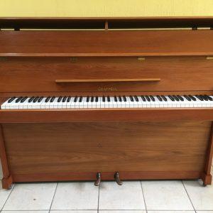 """Este lindo piano vertical Chappel modelo CX40 número de serie 88219 fue manufacturado en el año 1969 pero ha tenido muy poco uso y conserva su calidad y sonido distintivo de un piano británico de alta calidad.  Con un tono rico y lleno, sus 88 teclas de plástico intactas, su mueble de pintura original y acabado de """"teca satinado"""" en una veta natural, seguramente complacerá las demandas de cualquier pianista con estilo y elegancia. Las cuerdas de este piano están prácticamente nuevas, sin señal de óxido o polvo. Su sonoridad es moderada. Se siente suave al tocarlo y con una excelente respuesta a la velocidad, lo que lo hace ideal para todos los niveles de pianistas. Sus dimensiones son:Altura es de 119 cm, ancho de 135 cm, profundidad de 51 cm."""