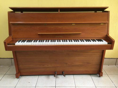 Este lindo piano vertical Chappel modelo CX40 número de serie 88219 fue manufacturado en el año 1969 pero ha tenido muy poco uso y conserva su calidad y sonido distintivo de un piano británico de alta calidad.  Con un tono rico y lleno, sus 88 teclas de plástico intactas, su mueble de pintura original y acabado de