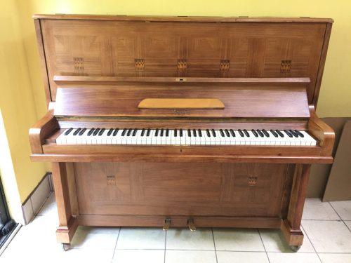 El piano fue construido con madera de nogal y decoración estilo Art Deco muy vanguardista para inicios de siglo, con un acabado semi glossy que preserva su estilo antiguo pero que luce elegante como una pieza invaluable que perdura por los años.