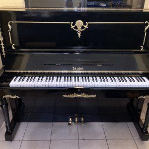 Piano negro vertical Saujin Deluxe producido por la compañía Daewoo alrededor de 1985, bellamente decorado con aplicaciones de madera, pintadas en color dorado está disponible para que pueda lucirlo en su sala de estar.