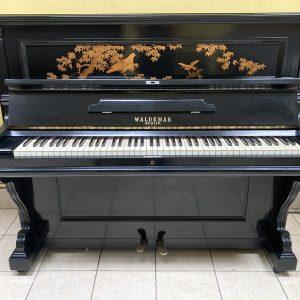 Este bello piano Waldemar de 1920 cuenta con una bella decoración de aves y plantas en madera incrustada que destaca en la tapadera frontal del piano.