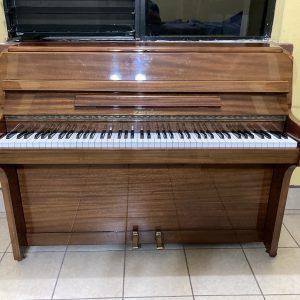 Fabricado en Londres, Inglaterra, este piano compacto Zender se presenta en una caja de caoba natural con acabado glossy brillante.